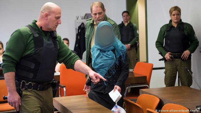 A woman accused of child abduction after taking her two young daughters to Syria enters the regional court in Munich.