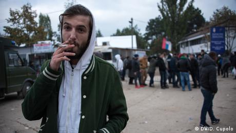 Presevo local Liridon Bizazli, an Albanian living in Kosovo, stands outside the Presevo refugee camp to sell bus tickets