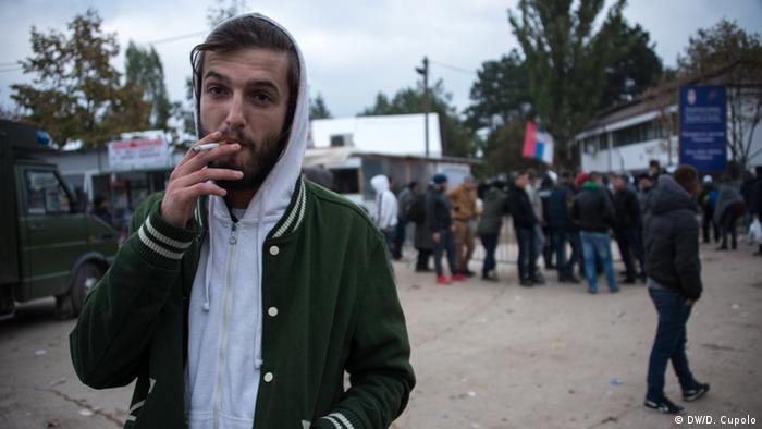 Liridon Bizazli lebt in Presevo. Als Albaner wohnt er im Kosovo. Er steht außerhalb eines Flüchtlingslagers und raucht eine Zigarette. (Foto: Diego Cupolo)