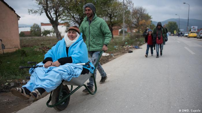 A young man pushes an elderly Kurdish woman in a wheelbarrow in Presevo