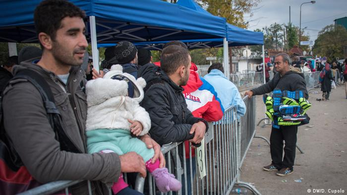 A shoe peddler offers his wares to refugees waiting in line to catch a bus