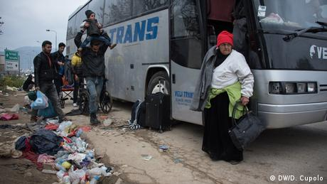 An elderly woman stands next to the door of a bus parked at the side of the road, which is covered in litter