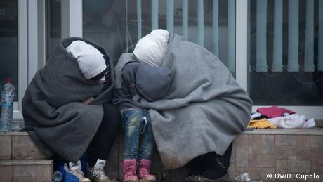 A family huddles wrapped in blankets in front of a shop front