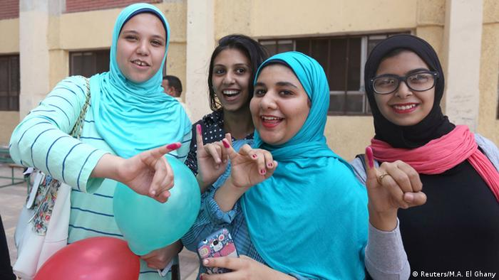 Women show the ink on their finger after voting during the run-off to the first round of parliamentary election in Imbaba, Giza