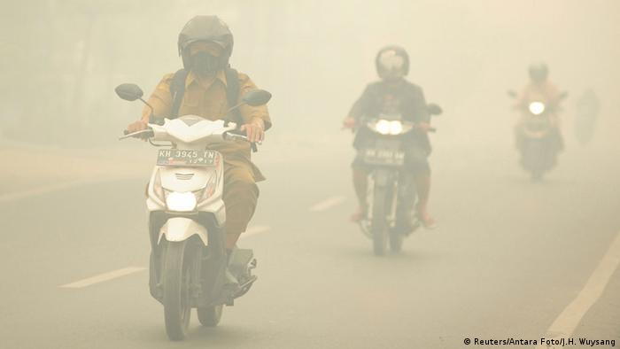 People ride motorcycles as haze shrouds the street in Palangkaraya, Central Kalimantan province, Indonesia (Photo: Reuters/Antara Foto/J.H. Wuysang)