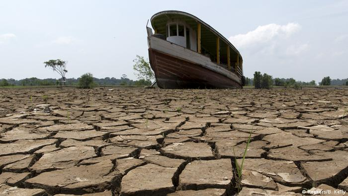 A boat resting on dry land at the bottom of the Amazon River during drought in October 2015