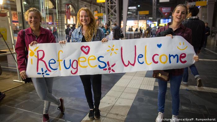 Девушки во Франкфурте-на-Майне с плакатом Беженцы, добро пожаловать