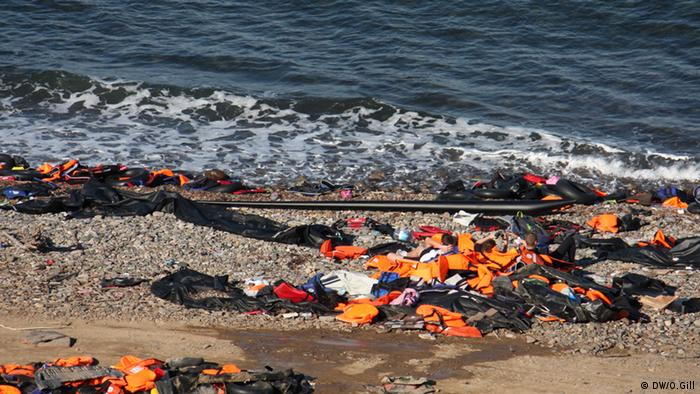 Helpers rest on the beach against a huge pile of lifejackets