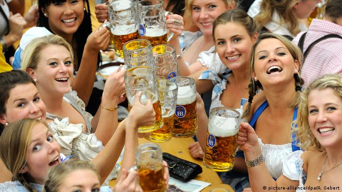 women smile and hold up their beer mugs (picture-alliance/dpa/A. Gebert)