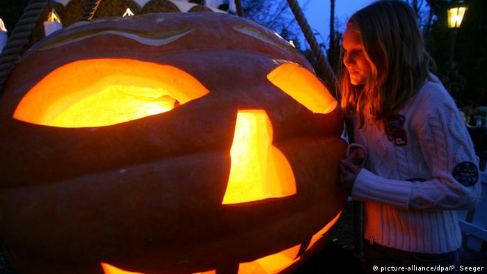 Girl looking into a great big, lit-up pumpkin (picture-alliance/dpa/P. Seeger)