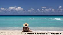 Ein Urlauber mit Strohhut blickt auf das türkisfarbene Meer und den blauen Himmel am Strand von Varadero auf Kuba, aufgenommen am 23.04.2013. Foto: Peter Zimmermann