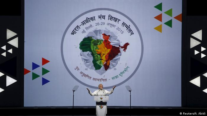 India's Prime Mnister Narendra Modi stands in front of a banner showing India and Africa maps entwined.