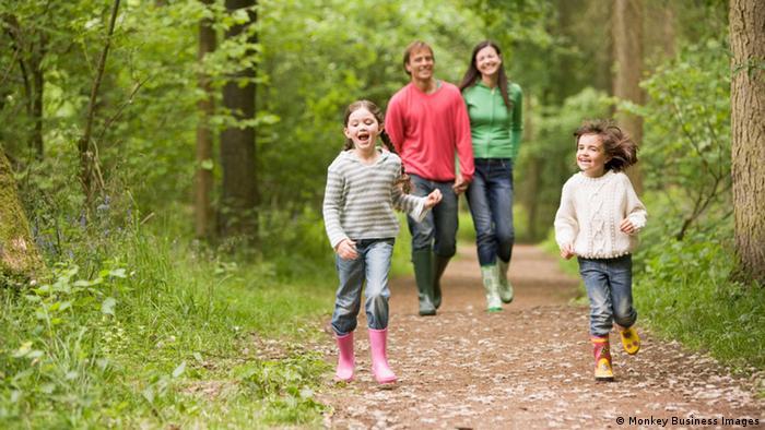 Eine Familie mit zwei Kindern geht im Wald spazieren