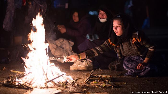 Беженцы греются у ночного костра