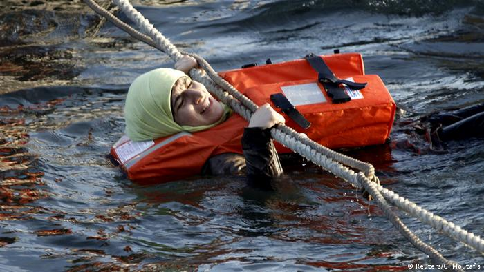 A refugee woman clings to a rope after the loaded boat she was on began sinking into the Aegean Sea.