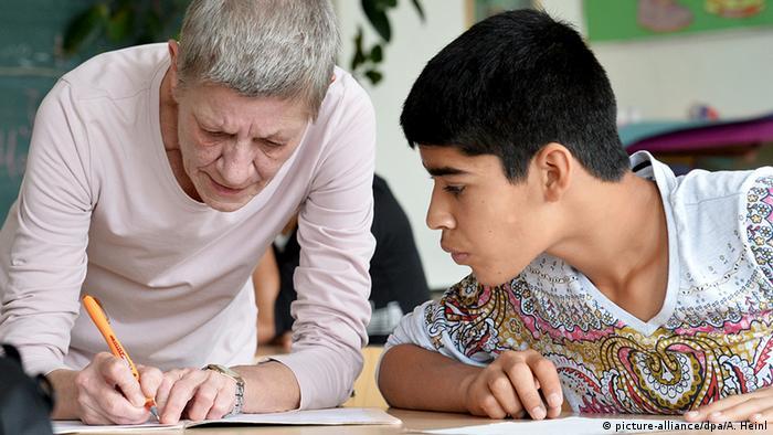 Eine Lehrerin hilft einem Flüchtling