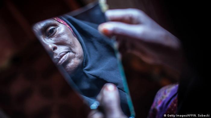 Cara de una mujer en un trozo de espejo roto.
