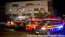 ***31.10.2015***CORRECTS TO REMOVE REFERENCE OF EXPLOSION - Ambulances are parked outside the site of a fire that occurred in a club, housed by the building in the background, in Bucharest, early Saturday, Oct. 31, 2015. A heavy metal band's pyrotechnical show sparked a deadly fire Friday at a Bucharest nightclub, killing more than 20 people and injuring scores of the club's mostly youthful patrons, officials and witnesses said. Copyright: picture-alliance/AP Photo/Vadim Ghirda