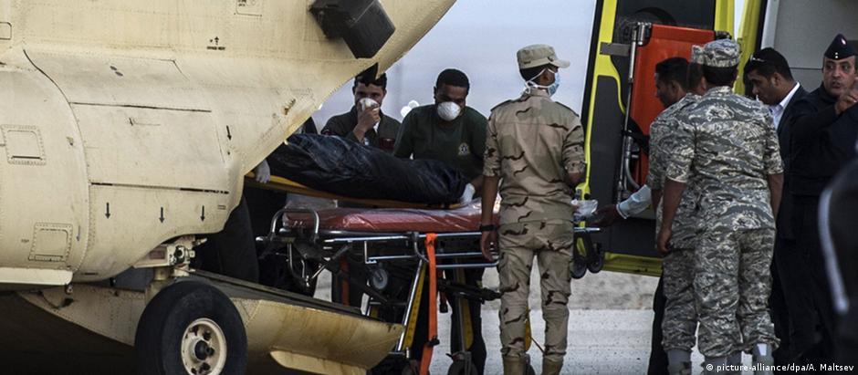 Equipes de resgate egípcias transportam corpo de vítima de desastre com avião russo
