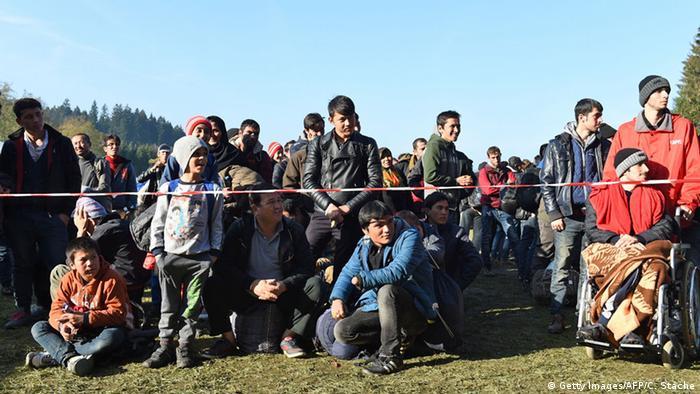 Беженцы ожидают разрешения на проход в Германию, сидя и стоя на траве возле границы