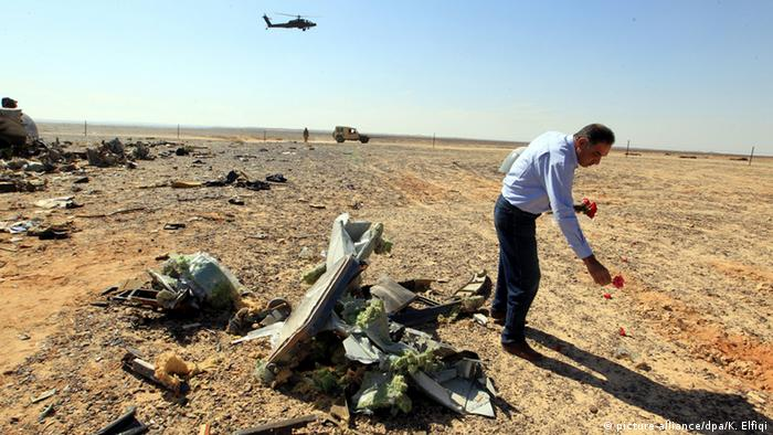 An Egyptian man lays flowers by the debris of the downed plane