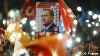 People wave flags and hold a portrait of Turkish President Tayyip Erdogan during a rally in Ankara.