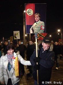Deutschland Pegida-Demonstrant mit anti-Merkel-Plakat in Dresden