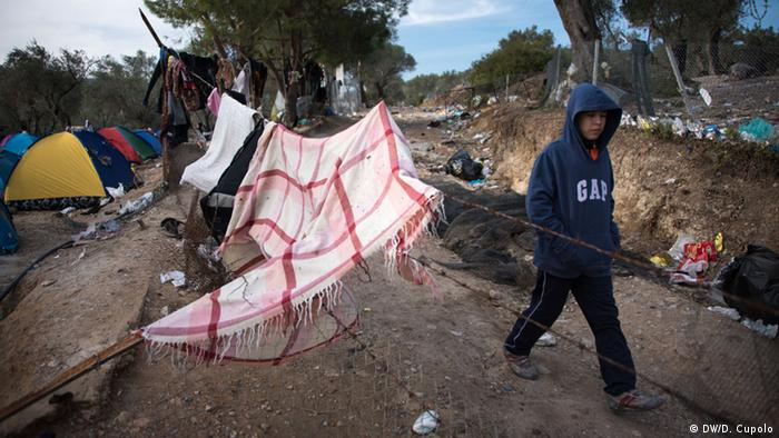 A boy walks past tents and blankets strung up between trees in a landscape littered with trash