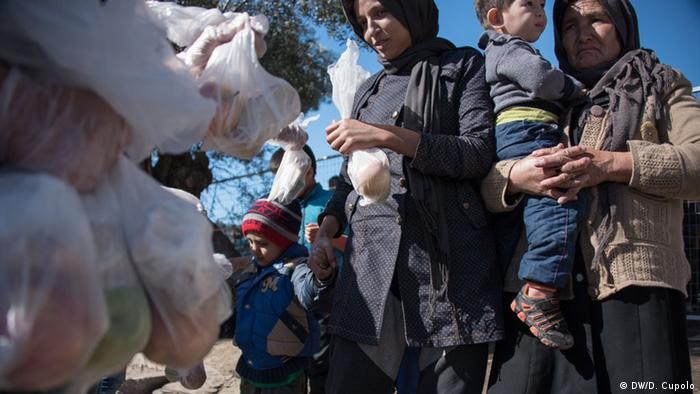 Women stand with children and receive small bags of food