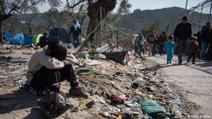 A boy sits on a mound of dirt strewn with trash with his head in his arms
