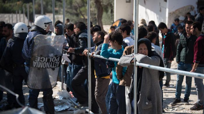 Refugees mill about waiting alongside police in riot gear