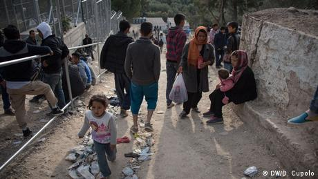 Men, woman and children mill around inside Moria refugee camp