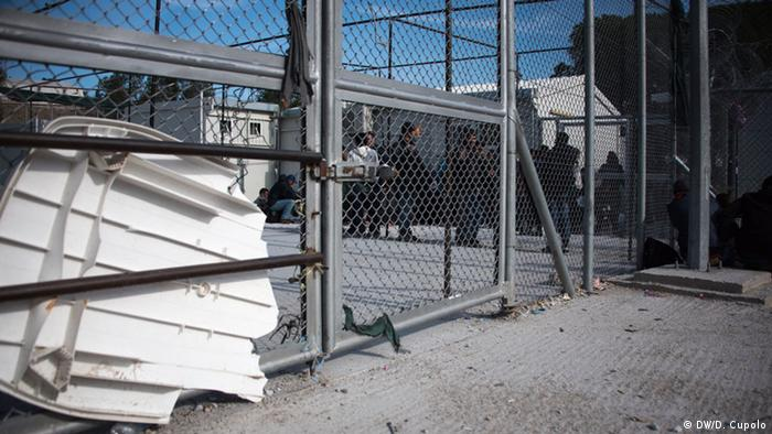 People stand inside a fenced-in compound
