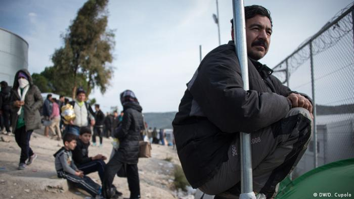 A men perches on a metal frame in front of tents and a fence