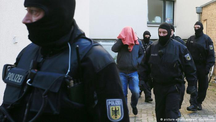 Masked police lead away a man, whose head is covered, during raids in Hildesheim