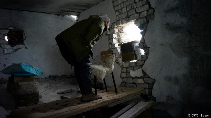 A Ukrainian marine peers at separatist positions through artillery damage in a former sanatorium