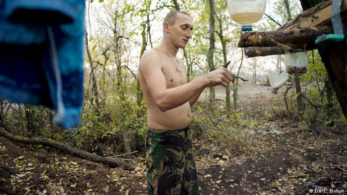 A marine shaves on an autumn morning on the Donetsk front