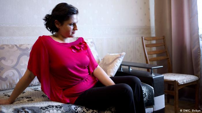 Katja sits in her Kyiv flat