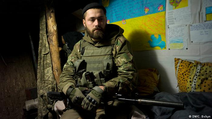 Maxim sits on his bed in an underground earth and wood bunker on the frontline