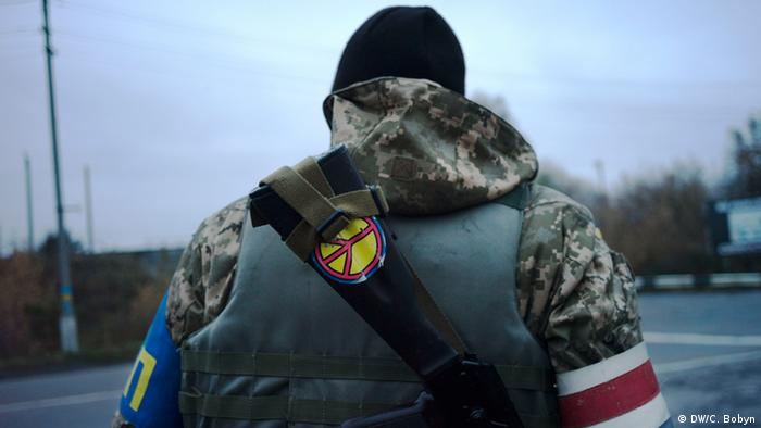 A government soldier mans a checkpoint in Donetsk. A peace sticker is visible on his back