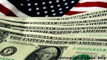 ARCHIV - ILLUSTRATION - US-amerikanische Geldscheine sind vor einer USA-Fahne zu sehen, aufgenommen am 14.07.2011 in Dresden. Die US-Notenbank Federal Reserve (Fed) hält sich ihre geldpolitischen Optionen weiter offen und lässt die Finanzmärkte damit im Unklaren. (zu dpa Niedrigzinsen und Gelddrucken in aller Welt am 28.10.2015) +++(c) dpa - Bildfunk+++ (C): picture-alliance/dpa/A. Burgi