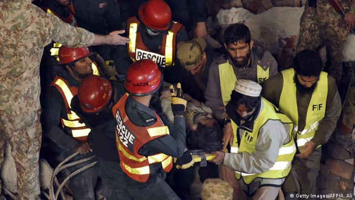 Pakistani rescuers remove a victim from the rubble of a collapsed factory on the outskirts of Lahore on November 4, 2015. At least 16 people were killed and 40 injured when a factory collapsed near the eastern Pakistani city of Lahore on November 4, officials said, with around a hundred more still trapped (Photo: Arif Ali/AFP/Getty Images)