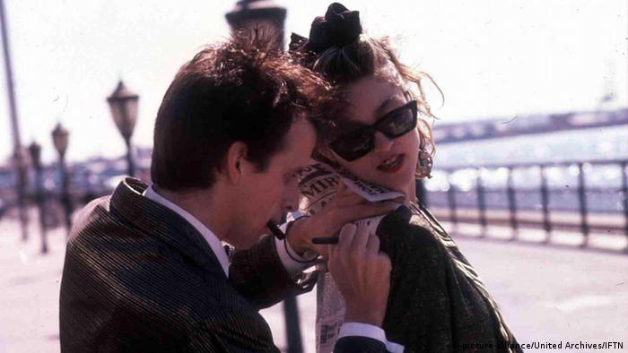 Madonna on the boardwalk as man writes on a newspaper on her back in 1985's Desperately Seeking Susan