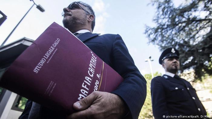Law suit begins against the mafia: man carrying a file, with a policeman to the side (Photo: picture-alliance/dpa/A. Di Meo)