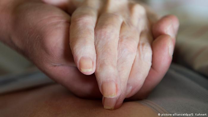 Человек держит за руку пожилую женщину