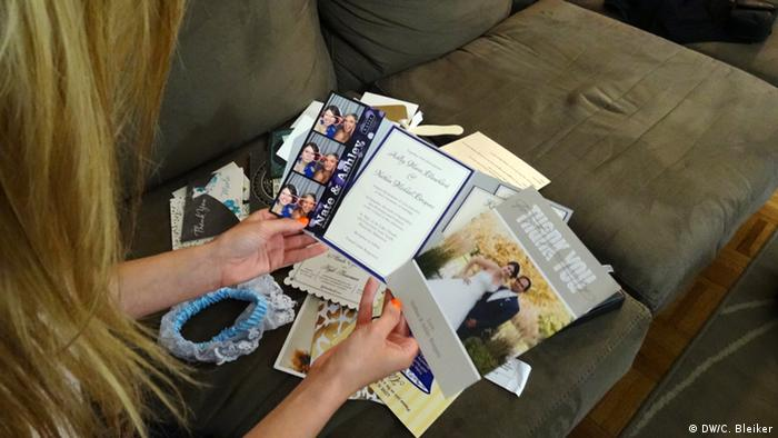 Jen Glantz looking at invitations and thank you cards from the weddings she's been to. (Photo: Carla Bleiker, DW)