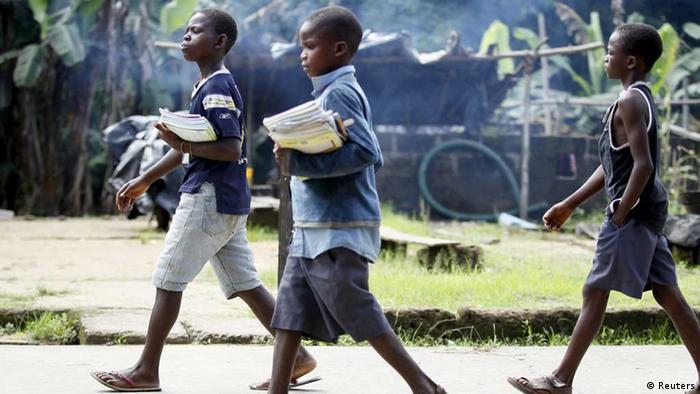 Boys holding school books walk home from school