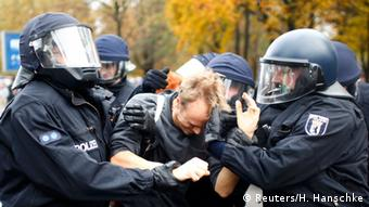Police officers hold on to a counter-demonstrator