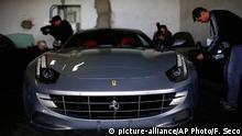 In this photo taken on Monday, Oct. 19, 2015, members of the media take images of one of the two Ferrari luxury cars donated by Spanish former King Juan Carlos to the National Heritage, in Madrid. Two Ferraris given as gifts to former King Juan Carlos are to be auctioned off by the Spanish state, with starting prices of some 350,000 euros ($400,000) each. The two Ferrari FF four-seater models are on display this week for potential buyers. The Finance Ministry says they will be auctioned on Nov. 6. Bidders will have to lodge deposits of about 17,500 euros. (AP Photo/Francisco Seco)