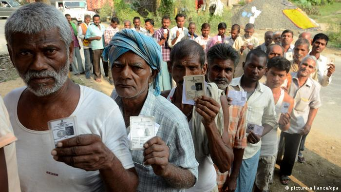 Indian voters show their voter ID cards while waiting to vote at Samastipur, Bihar in 2015. Indien Bihan Wahlen (picture-alliance/dpa)